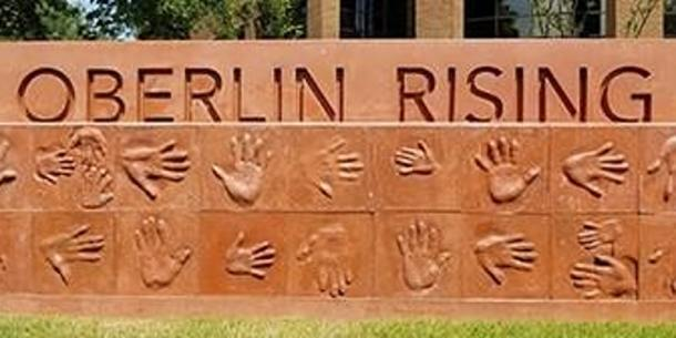 Sign of Oberlin Rising park with different patterns of hands beneath the sign.
